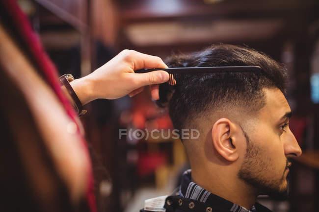 El hombre que se corta el pelo en la peluquería - foto de stock