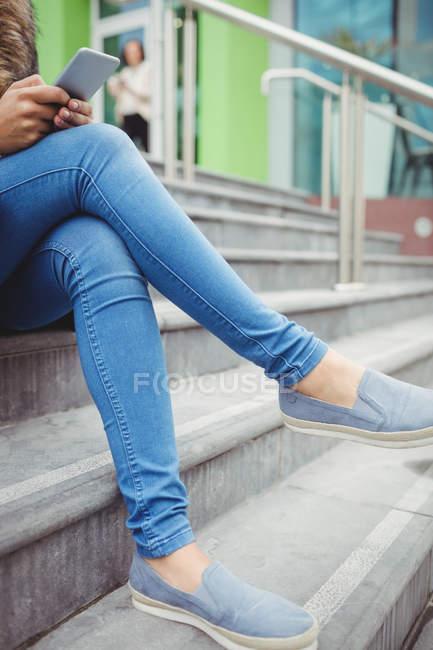 Низкая часть женщины с помощью телефона сидя на шагах — стоковое фото