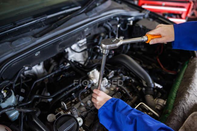 Imagen recortada del motor mecánico de mantenimiento del coche en el garaje de reparación - foto de stock