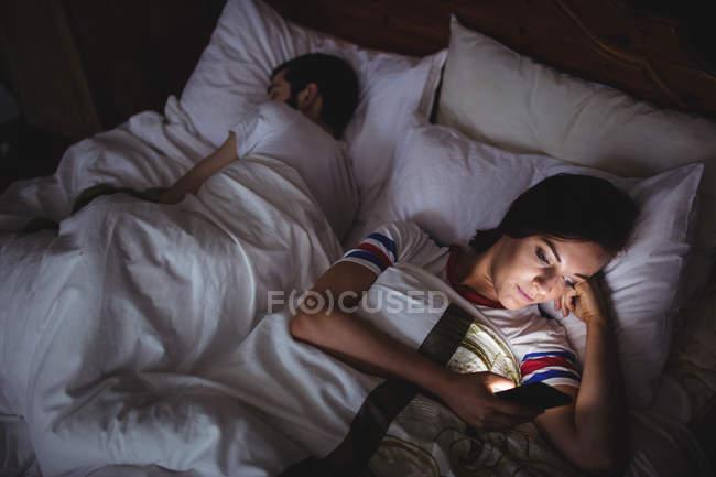 Donna che utilizza il telefono cellulare mentre sdraiato sul letto in camera da letto — Foto stock