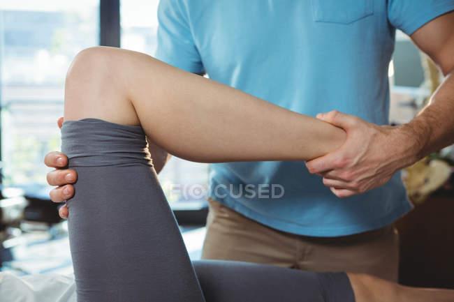 Imagen recortada de fisioterapeuta masculino dando masaje de rodilla a paciente femenino en clínica - foto de stock
