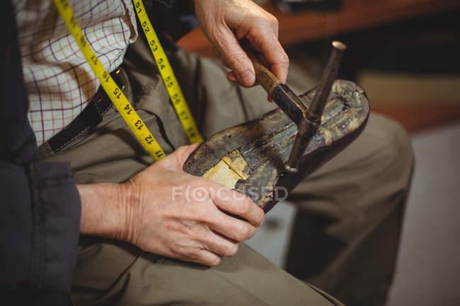 Mãos de sapateiro martelando em um sapato na oficina — Fotografia de Stock