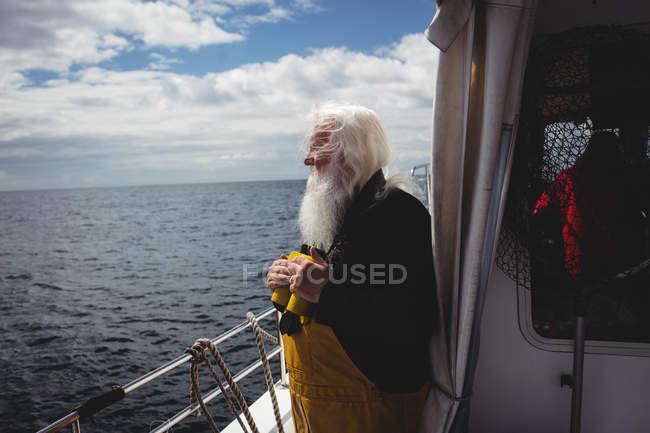 Fischer mit Fernglas und Blick auf das Meer vom Boot aus — Stockfoto