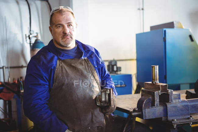 Portrait of welder holding electric saw in workshop — Stock Photo
