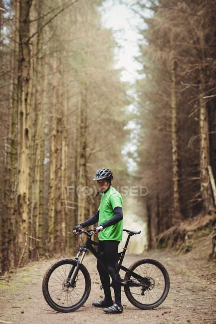 Горный велосипедист едет по грунтовой дороге среди деревьев в лесу — стоковое фото