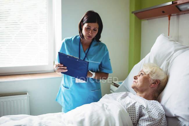 Enfermeira interagindo sobre um relatório com paciente sênior no hospital — Fotografia de Stock