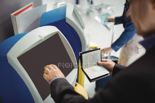 Homme d'affaires à l'aide de self service machine d'enregistrement automatique à l'aéroport — Photo de stock