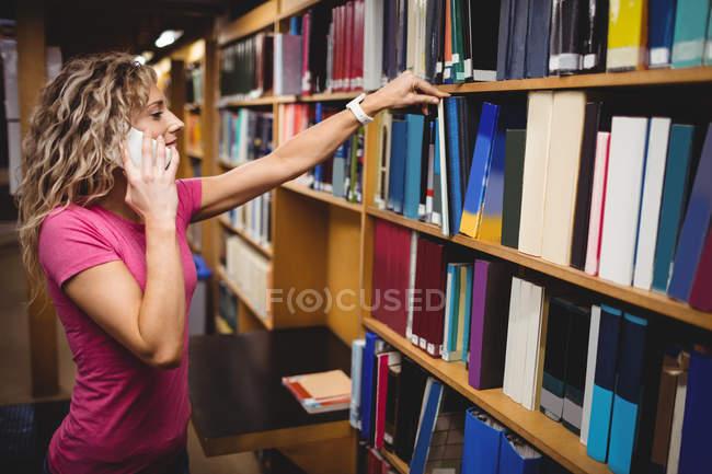 Donna parla al telefono cellulare durante la rimozione di libro da scaffale per libri in libreria — Foto stock