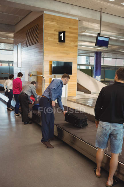 People taking their luggage off the baggage carousel at airport — Stock Photo