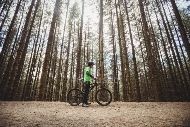 Side view of mountain biker on dirt road against trees in forest — Stock Photo