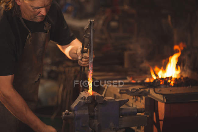 Blacksmith working on a heated iron rod in workshop — Stock Photo