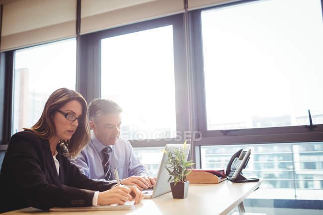 Uomo d'affari discutendo con il collega sul computer portatile in carica — Foto stock