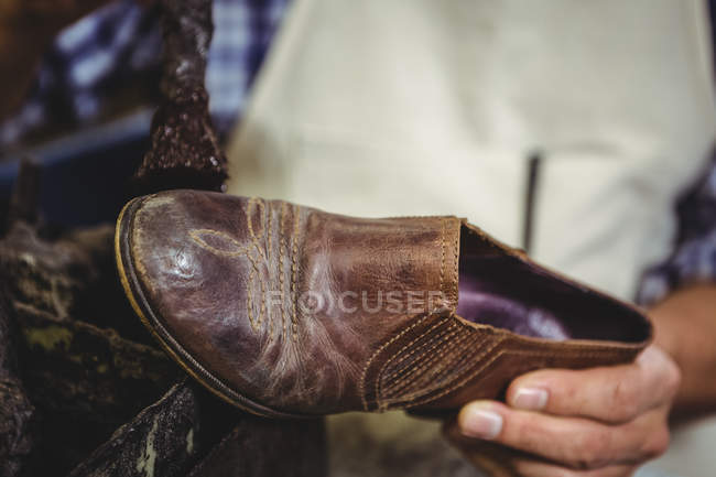 Close-up of shoemaker polishing a shoe in workshop — Stock Photo
