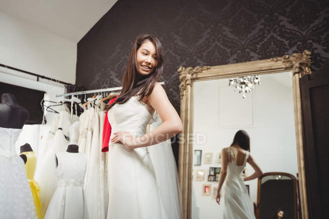 Smiling woman trying on wedding dress in shop — Stock Photo