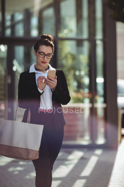 Businesswoman with bag using mobile phone outside office building — Stock Photo