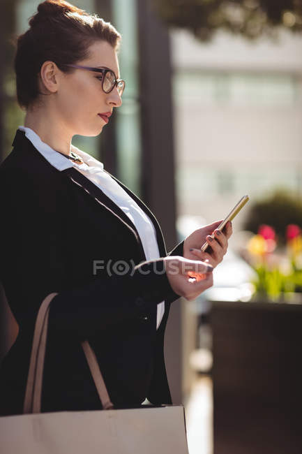Young businesswoman with bag using mobile phone — Stock Photo