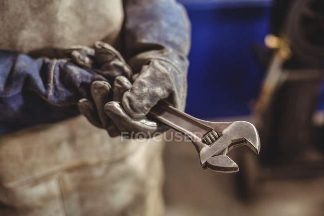 Міделю жіночий зварювальник тримає інструмент гайковий ключ у майстерні — стокове фото