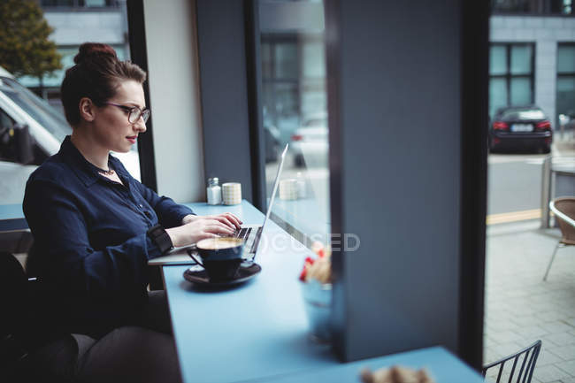 Young businesswoman working on laptop in cafe — Stock Photo