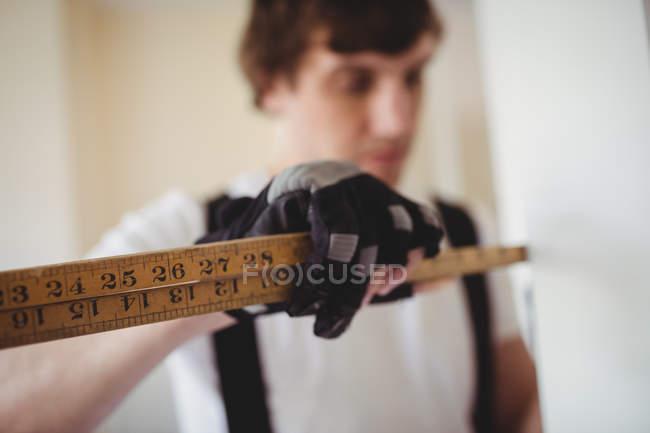 Selective focus of Carpenter measuring wooden door at home — Stock Photo