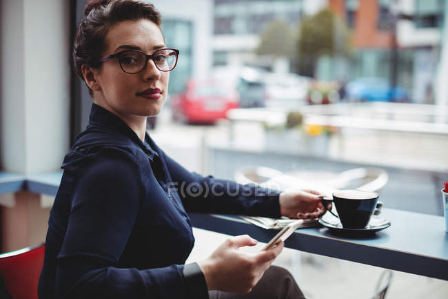 Portrait of businesswoman holding mobile phone in cafe — Stock Photo