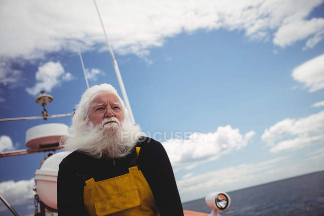 Nachdenklicher Fischer sitzt an Deck und schaut weg — Stockfoto