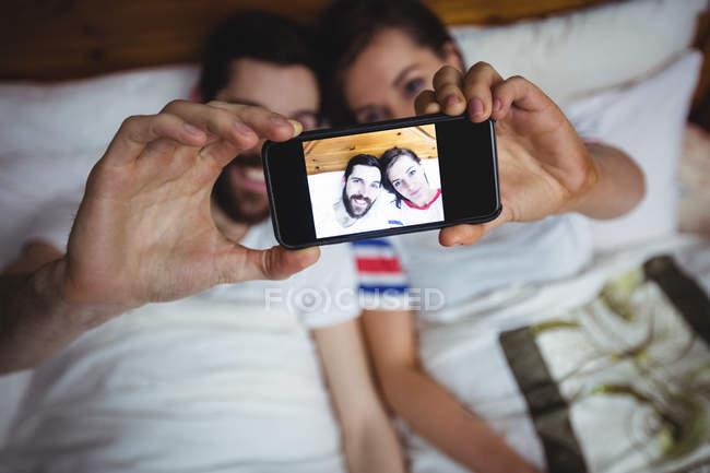 Пара, делающая селфи с мобильного телефона на кровати в спальне — стоковое фото