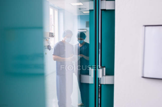 Surgeons discussing over digital tablet in a hospital — Stock Photo