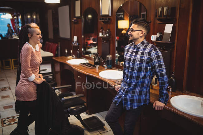 Two smiling barbers interacting with each other in barber shop — Stock Photo