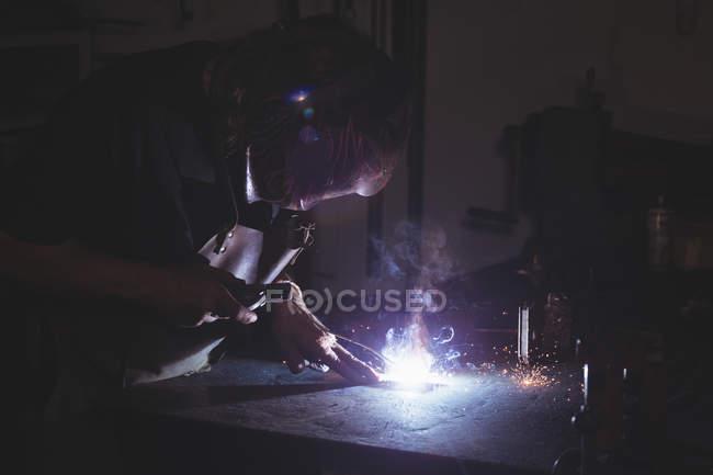 Кузнец сварки металла в мастерской — стоковое фото