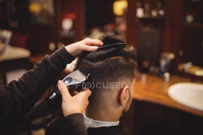 Uomo ottenere i capelli tagliati con trimmer in negozio di barbiere — Foto stock