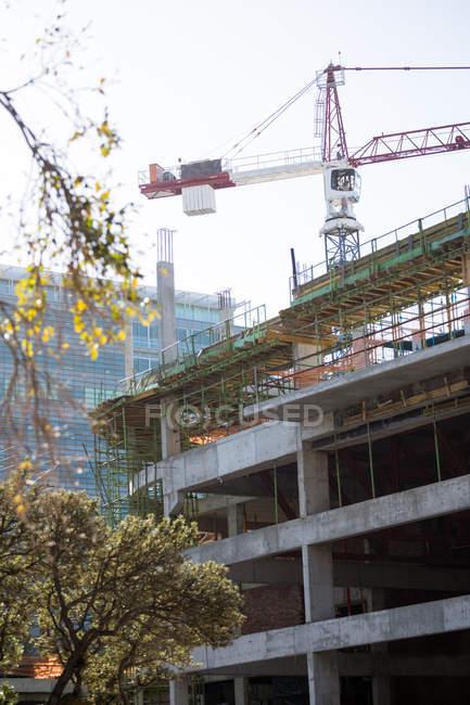 Кран и строительная площадка при дневном свете — стоковое фото