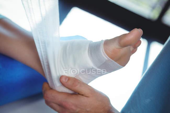 Imagen recortada de terapeuta masculino poniendo vendaje en pie de paciente femenino en la clínica - foto de stock