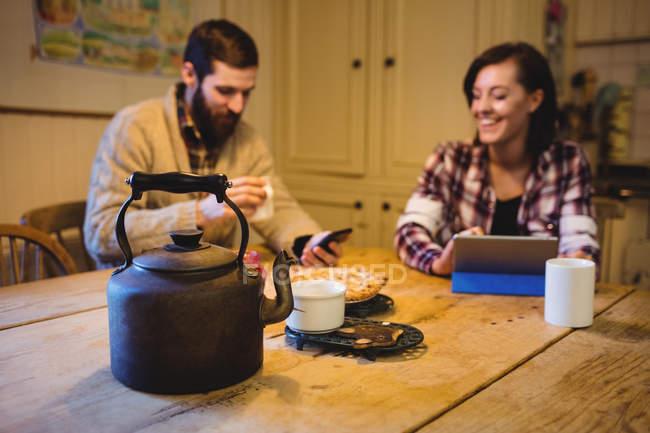 Mann und Frau nutzen digitales Tablet und Handy zu Hause — Stockfoto