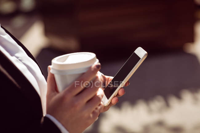 Cropped image of woman holding mobile phone and disposable coffee cup — Stock Photo