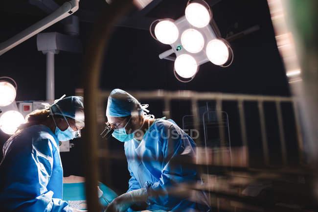 Cirurgiões que realizam operação em sala de operação no hospital — Fotografia de Stock