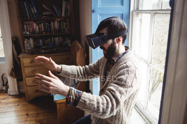 Молодий чоловік, за допомогою віртуальних окуляри вдома біля вікна — стокове фото