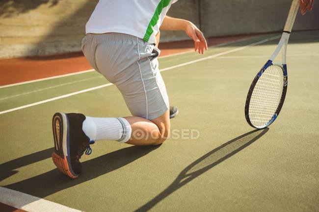 Homem ajoelhado na corte enquanto joga tênis à luz do sol — Fotografia de Stock