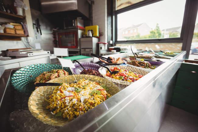 Gekochtes Essen auf Tellern am Schalter im Supermarkt — Stockfoto