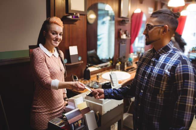 Uomo che paga con la carta di credito nel negozio di barbiere — Foto stock