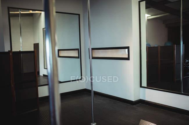 Vertical poles in empty fitness studio — Stock Photo
