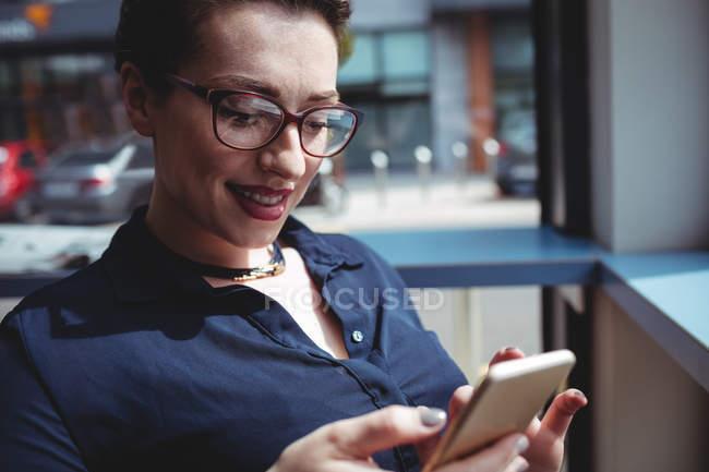 Mujer joven sonriente usando el teléfono móvil en la cafetería - foto de stock