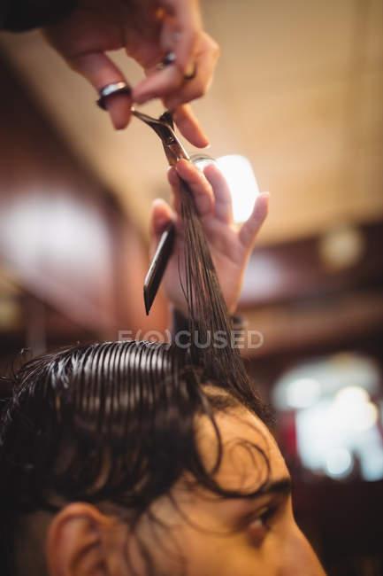 Homme se faire couper les cheveux avec des ciseaux dans le salon de coiffure — Photo de stock