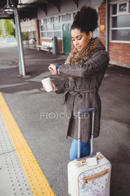 Женщина проверяет время, стоя на платформе вокзала — стоковое фото