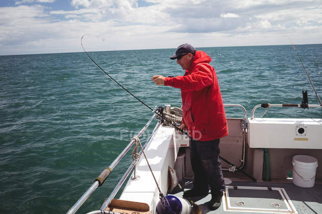 Side view of Fisherman fishing with fishing rod from boat — Stock Photo