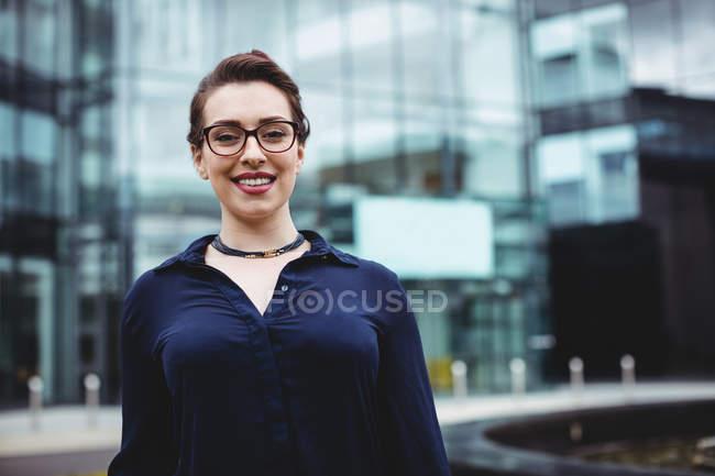 Портрет улыбающейся деловой женщины, стоящей у офисного здания — стоковое фото