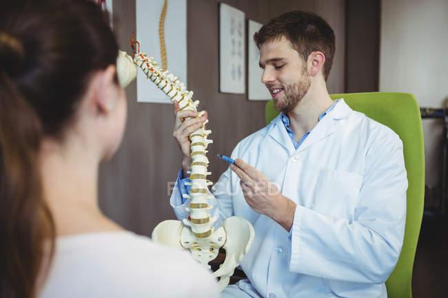 Physiotherapeutin erklärt Patientin in Klinik die Wirbelsäule — Stockfoto