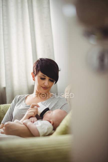 Madre alimentando al bebé en la sala de estar en casa - foto de stock