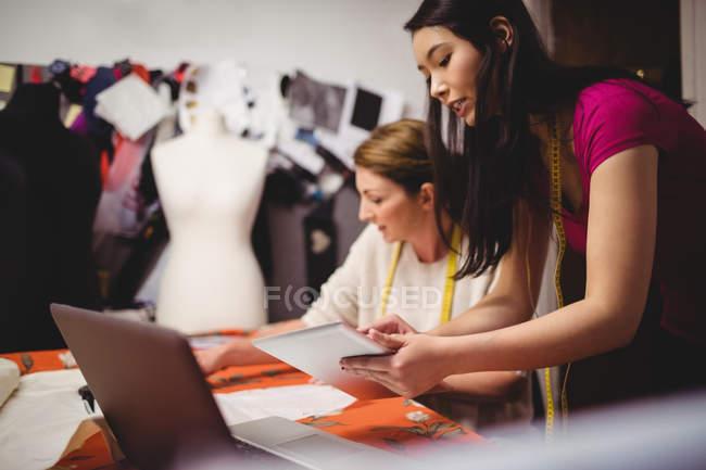 Female fashion designers working on laptop in studio — Stock Photo