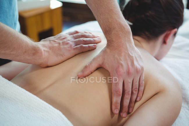 Close-up of physiotherapist giving physical therapy to back of female patient in clinic — Stock Photo