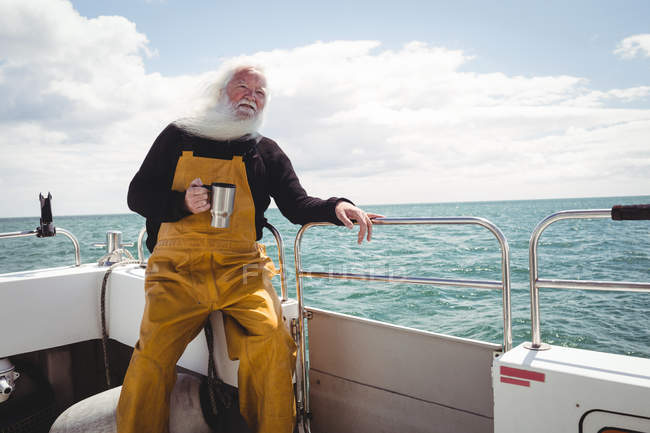 Fisherman holding cup of coffee on boat — Stock Photo